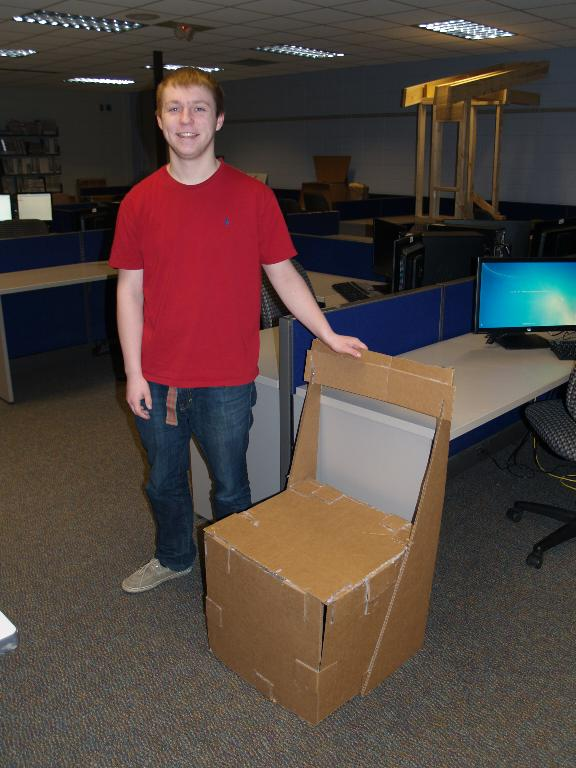 This is a picture of a male student with his cardboard chair he designed