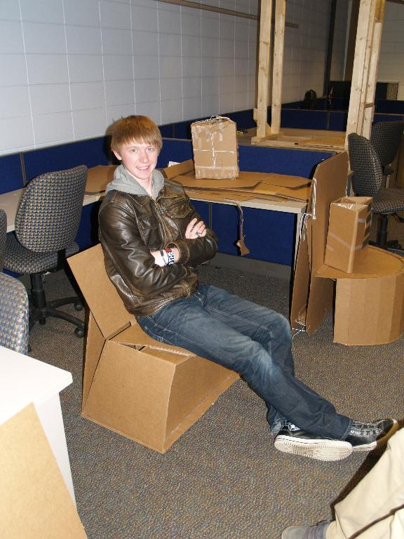 This is another picture of a male student with his cardboard chair he designed