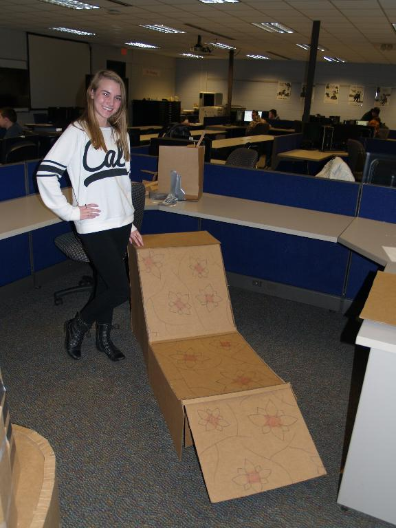 This is a picture of a female student with her cardboard chair she designed