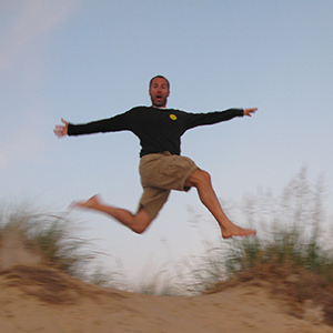 Mr. Petz jumping in the air from a sand dune.