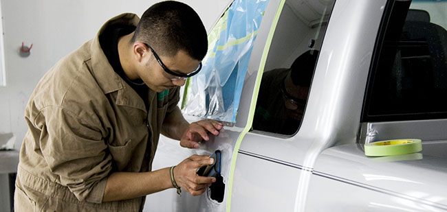 Student repairs a dent in a pickup truck