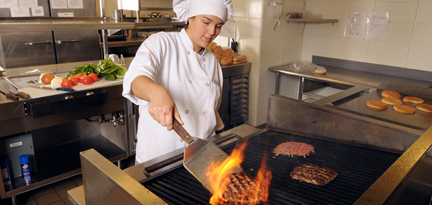 Grilling burgers for diners in the Culinary Cafe