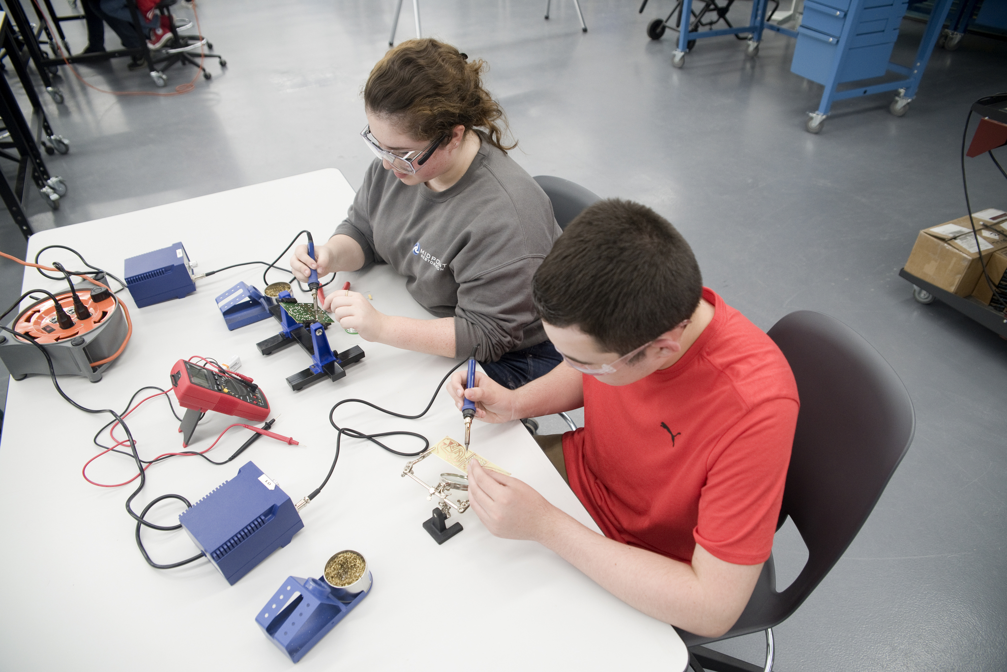 two students soldering electronics