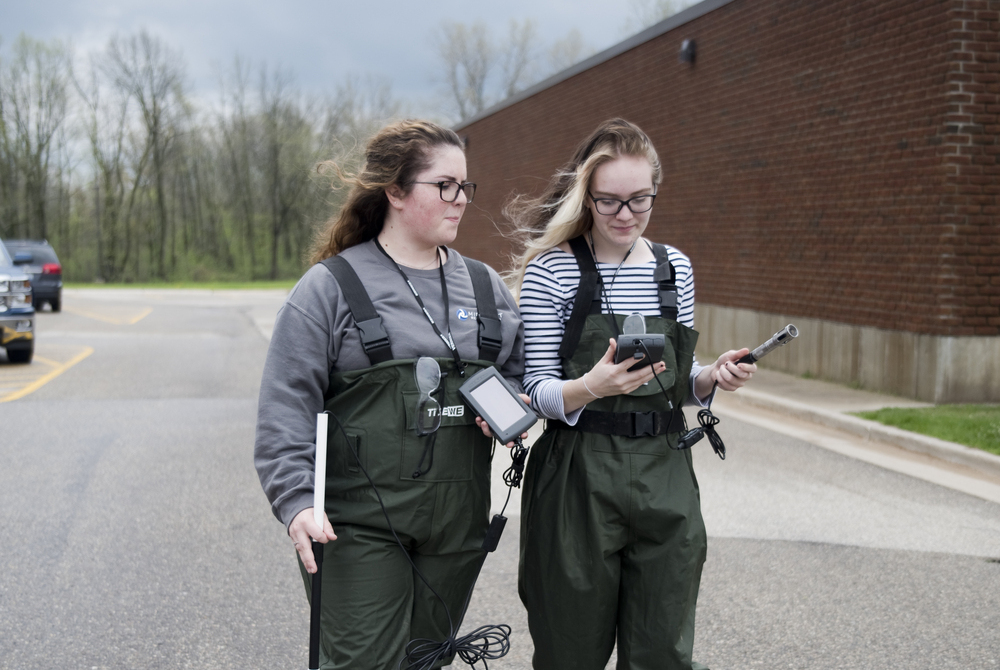 two girls in waders with water quality testing equipment
