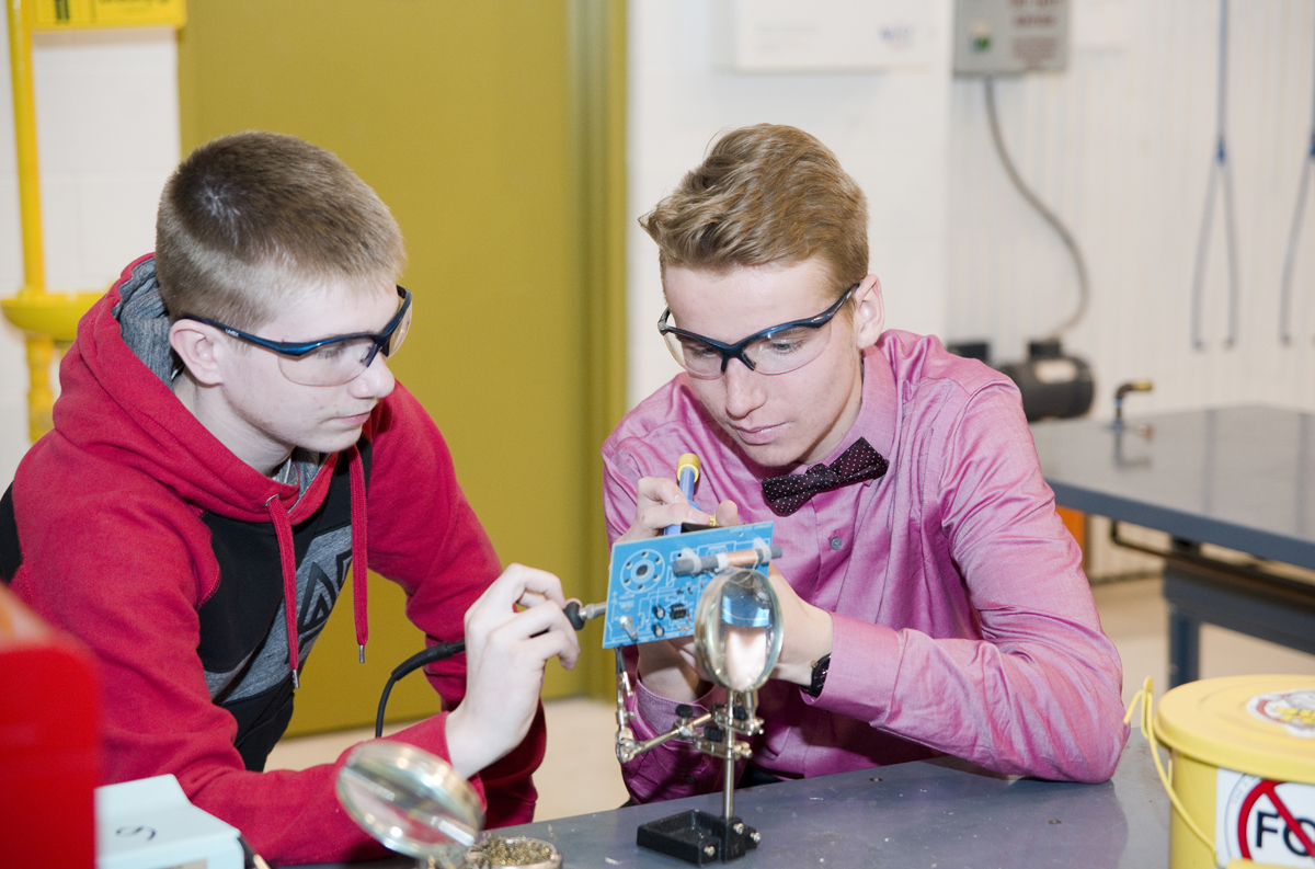 Students soldering components