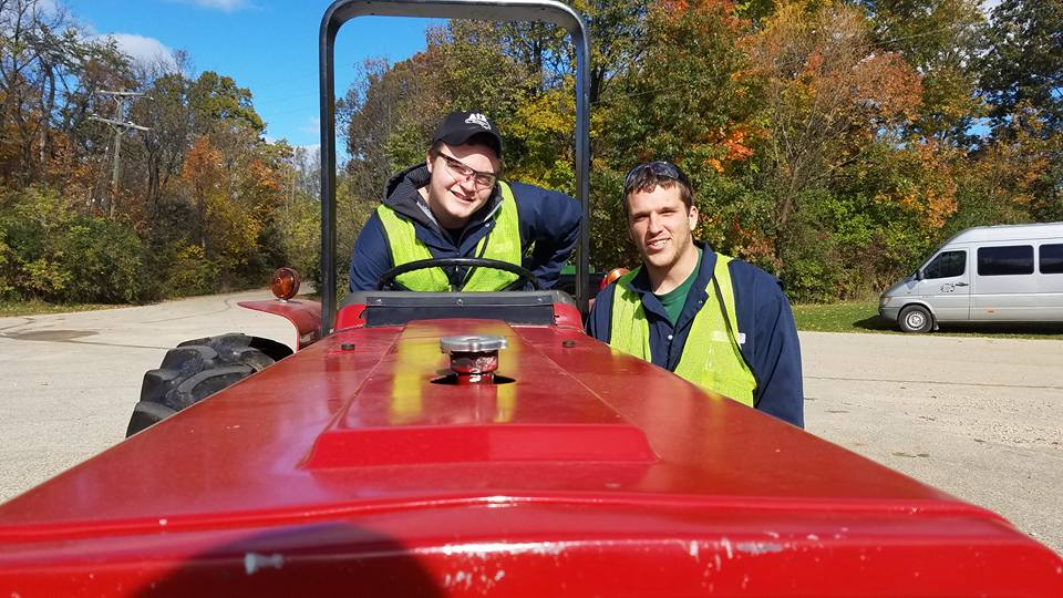 2 students posing for picture during operation of our Case 485 Tractor.