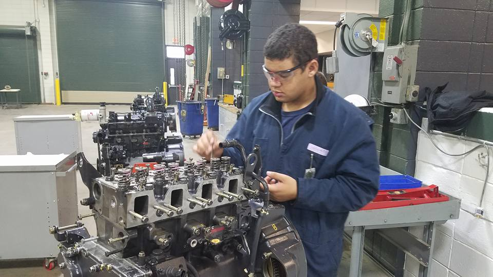 Picture of student removing push rods from the engine he is working on during the disassembling process.