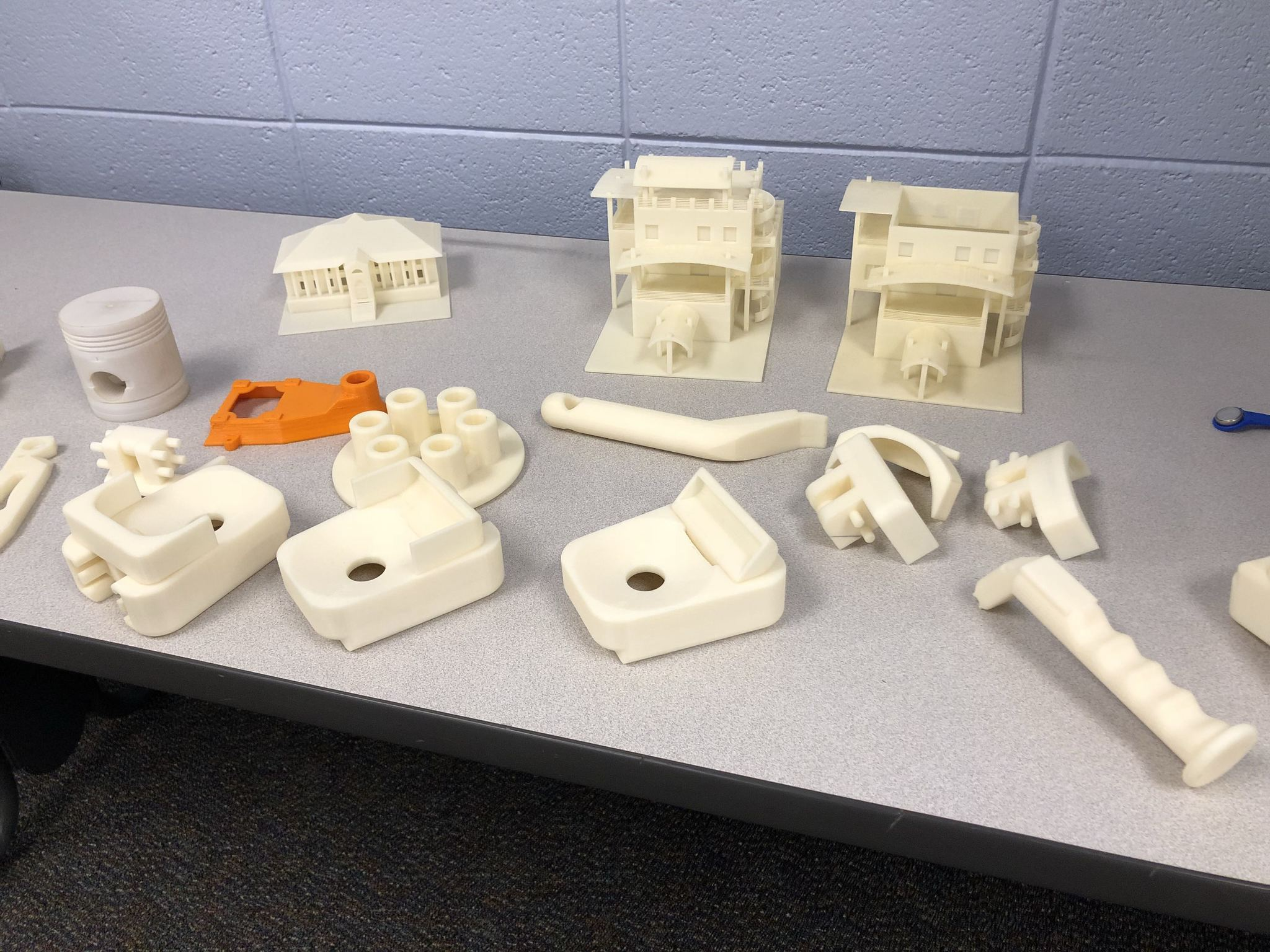 A variety of 3D printed parts, mostly white plastic, are arranged on a table top.