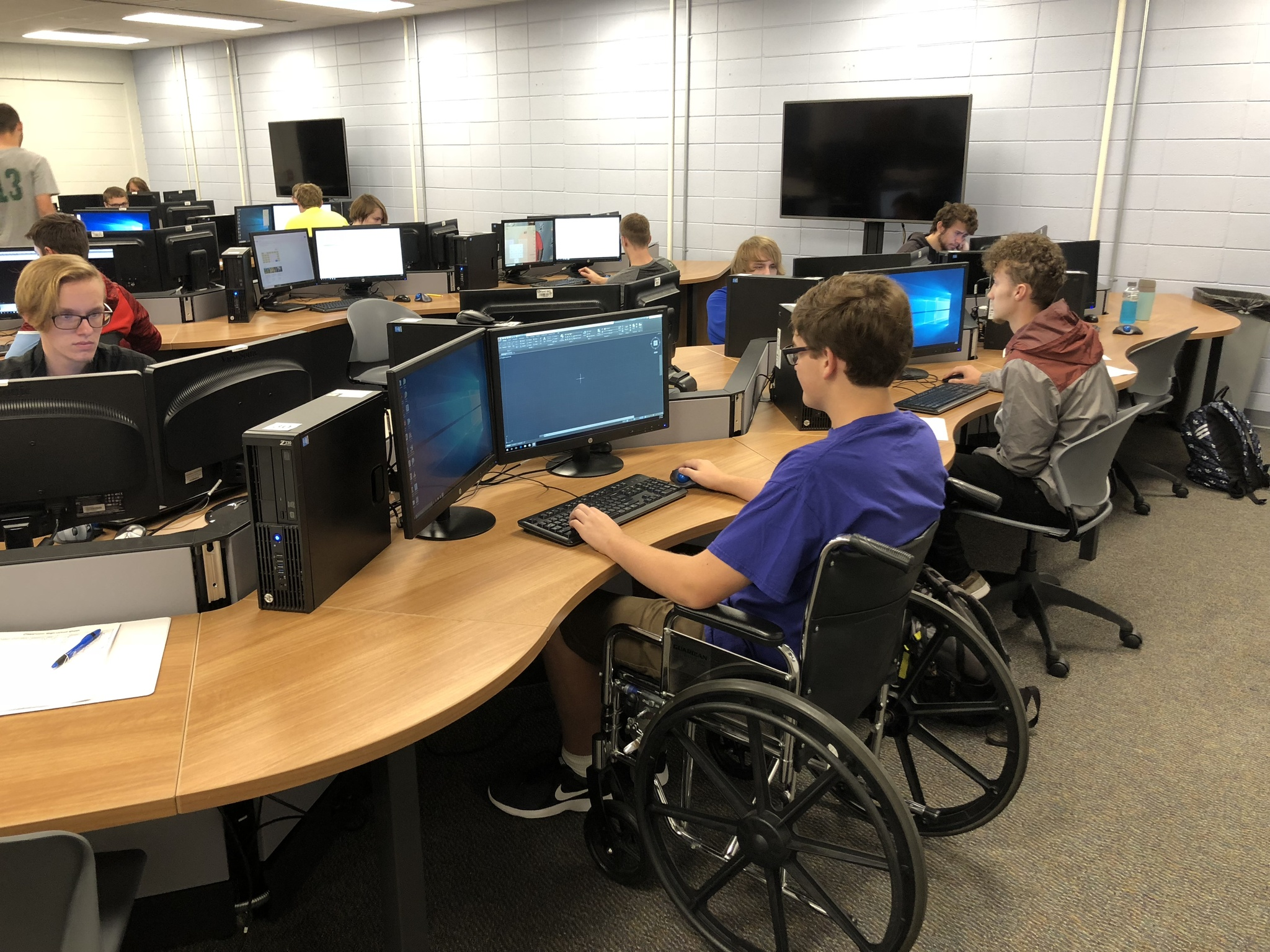 A student in a wheelchair is working on a design project at one of the new workstations. Other students are also working in the background.