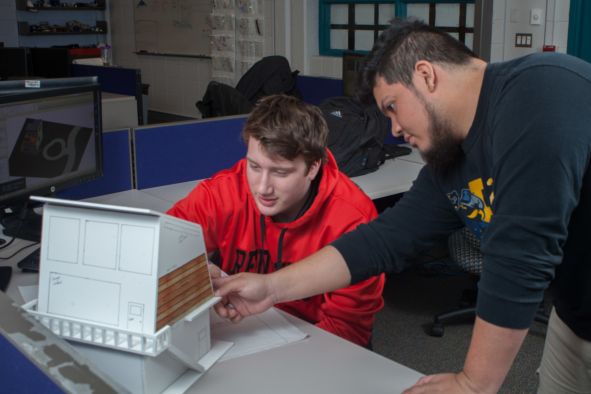 Two male students are discussing design ideas or revisions to an architectural house model at a classroom workstation.